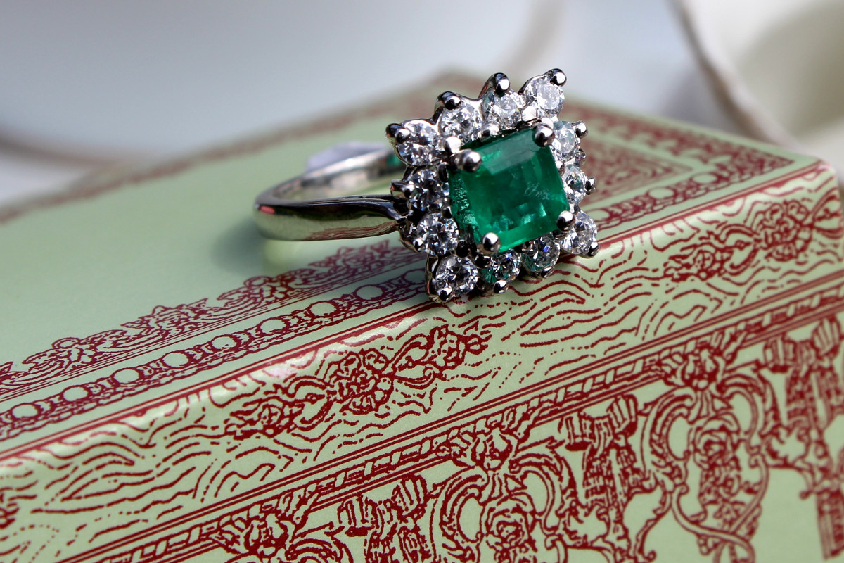 Bague de style Art Déco. Entourage diamants autour d'une belle émeraude taille princesse.